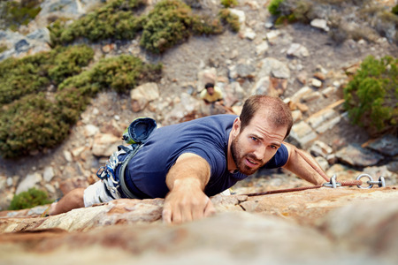 Photo for A man reaching for a grip while he rock climbs on a steep cliff - Royalty Free Image