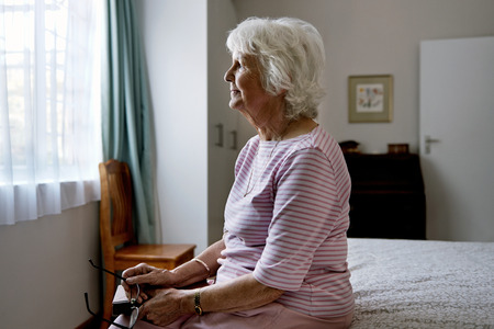 Foto de A solemn elderly woman sitting on her bed dealing with depression - Imagen libre de derechos