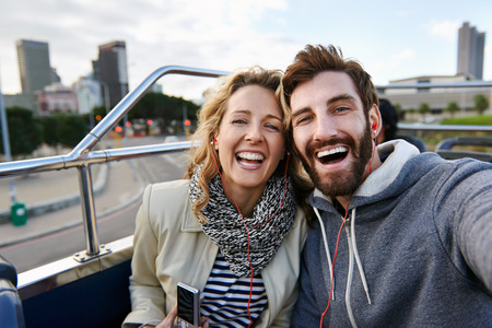 Foto de tourist couple travel selfie on open top tour bus in city - Imagen libre de derechos