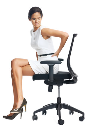Photo pour Businesswoman with lower back pain from sitting on office chair - image libre de droit