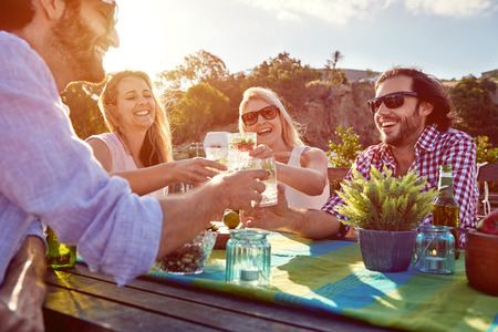 Foto de Group of friends toasting to a celebration with drinks while hanging out at a restaurant on a rooftop terrace - Imagen libre de derechos
