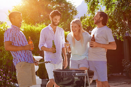 Photo for group of friends having outdoor garden barbecue laughing with alcoholic beer drinks - Royalty Free Image