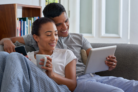 Photo pour smiling couple with tablet computer on sofa couch at home - image libre de droit