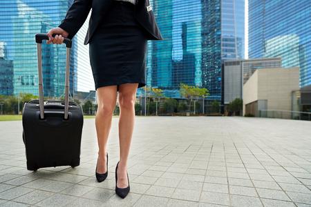 Photo pour travel business woman pulling suitcase bag walking along sidewalk outdoors in urban city - image libre de droit