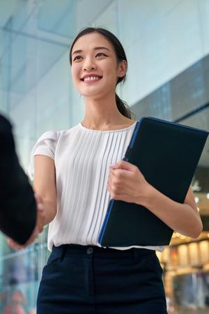 Foto de beautiful asian chinese business woman shaking hands in modern city work office - Imagen libre de derechos