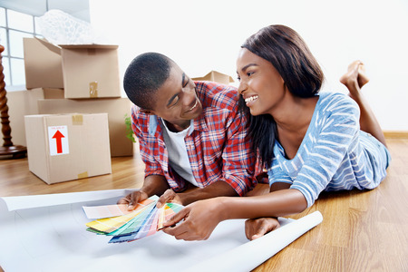 Photo for young african couple having fun deciding on paint colour swatch for new home apartment - Royalty Free Image
