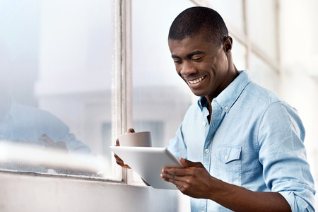 Foto de young successful black african man with morning coffee and tablet computer checking on news of investments - Imagen libre de derechos