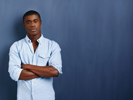 Photo for confident african man with arms crossed standing against blue wall for copyspace - Royalty Free Image