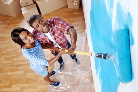 Foto de high overhead view of young black couple painting wall with roller in new house - Imagen libre de derechos