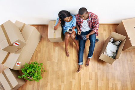Photo pour overhead view of young black african couple with moving boxes in new apartment using modern tablet computer technology - image libre de droit