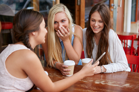Photo for beautiful young girls having coffee at outdoor cafe with mobile cell phone - Royalty Free Image