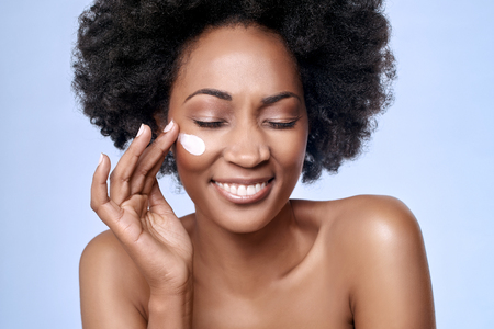 Photo pour Beautiful black african model with flawless skin smooth complexion applying moisturiser face cream to her cheek - image libre de droit