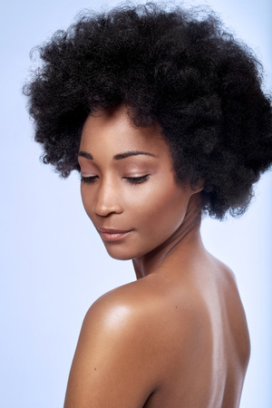 Bare shoulders  of beautiful black african model with afro in studio with smooth complexion flawless skin