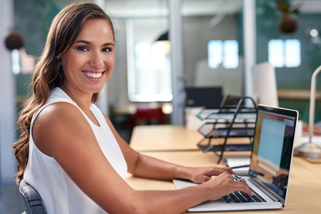 Foto de portrait of beautiful young business woman working on laptop computer at office desk - Imagen libre de derechos