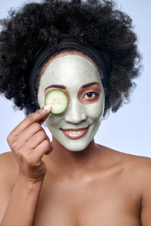 Foto de Portrait of beautiful black african model with a facial face mask holding a cucumber slice to her eye - Imagen libre de derechos