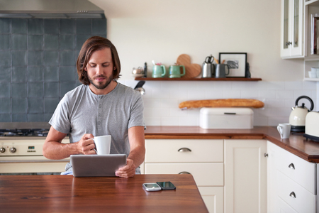 Photo pour young man enjoying morning coffee with tablet computer in home kitchen - image libre de droit