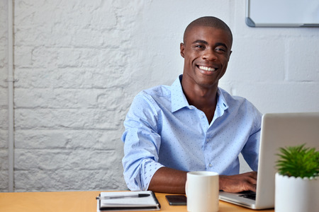 Photo for portrait of handsome African black young business man working on laptop computer at office desk - Royalty Free Image