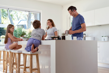 Photo pour happy smiling caucasian family in the kitchen preparing breakfast - image libre de droit