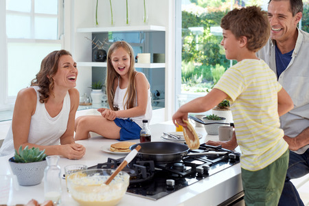 Photo for Happy caucasian family standing around stove, son making pancakes on stove - Royalty Free Image