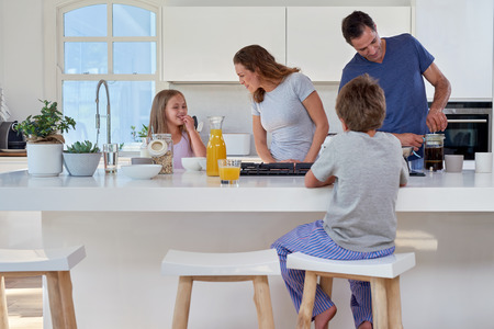 Photo for happy smiling caucasian family in the kitchen preparing breakfast - Royalty Free Image