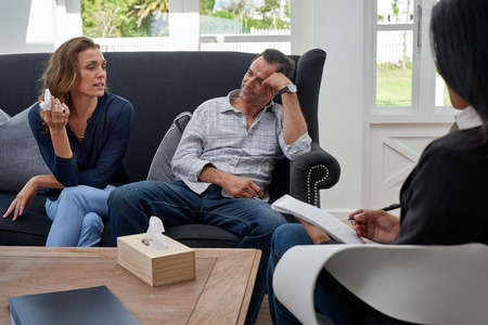 Foto de mature couple seated on couch, woman crying during therapy session - Imagen libre de derechos