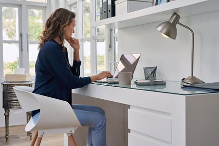 businesswoman entrepreneur working on laptop from home office space