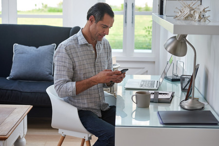 Photo pour Mature handsome man looking at mobile cell phone while at home in office work space - image libre de droit