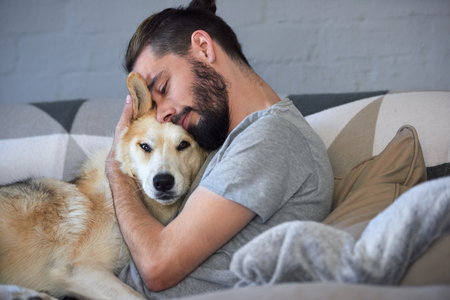 Photo for hipster man snuggling and hugging his dog, close friendship loving bond between owner and pet husky - Royalty Free Image
