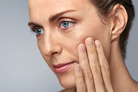 Photo pour Attractive middle aged woman touching her cheek skin, mature beauty concept - image libre de droit