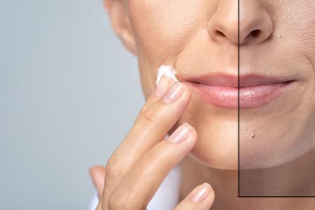 Foto de anonymous woman applying face cream, studio beauty skin care concept - Imagen libre de derechos