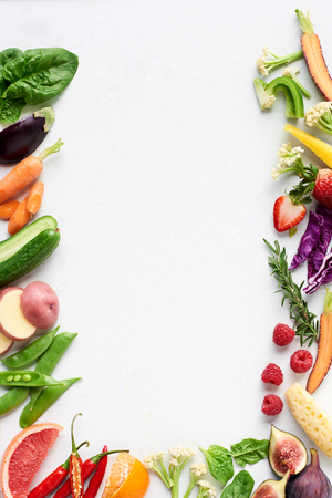 Photo pour Food background border flatlay of rainbow coloured fresh fruits and vegetables, carrot chilli cucumber purple cabbage spinach rosemary herb, plenty of copy-space - image libre de droit