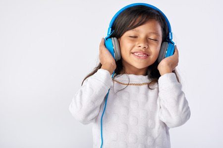 Photo for young girl playing her favorite song on headphones isolated in studio - Royalty Free Image