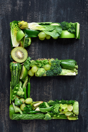 Photo pour complete collection of alphabet letters made from healthy green fruit and vegetables on rustic distressed texture, overhead flat lay - image libre de droit