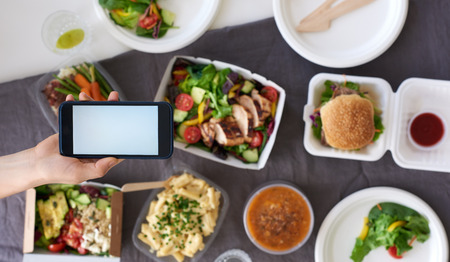 Photo pour Hands holding smartphone mobile cellphone over different types of gourmet takeout, food delivery order app application concept - image libre de droit
