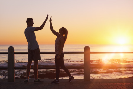 Foto de Friends high five celebrating the end of their run along the ocean at sunset, orange glow sun flare on horizon - Imagen libre de derechos