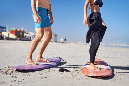 Photo pour anonymous couple learning how to surf, legs  standing up on surfboards on the beach - image libre de droit