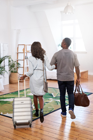 Photo pour Black couple checking out their holiday rental apartment, hug and happy to be on vacation honeymoon together - image libre de droit