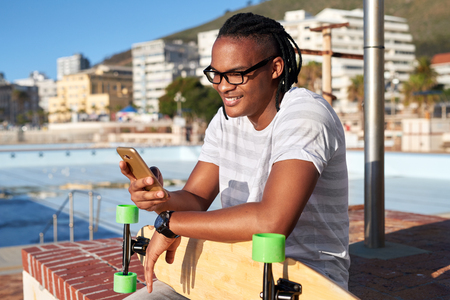 Foto de Man with longboard smiling and texting on mobile cell phone, sunny summer day - Imagen libre de derechos