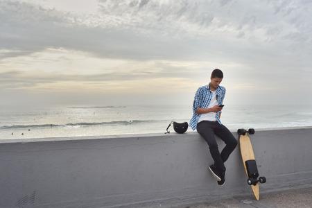 Photo pour Man with electric skateboard at the beach - image libre de droit
