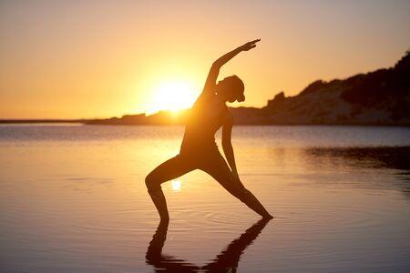 Foto de Yoga stretch woman silhouette at the beach healthy welness concept - Imagen libre de derechos