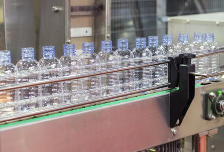 Photo for PET water bottle in conveyor of labelling machine  - Royalty Free Image