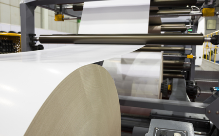 Photo for roll of white paper in modern paper cutting machine - Royalty Free Image