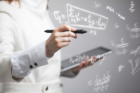 Foto de Woman scientist or student working with various high school maths and science formula. - Imagen libre de derechos