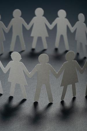 Foto de Circle of paper people holding hands on dark surface. Community, union concept. Society and support. - Imagen libre de derechos