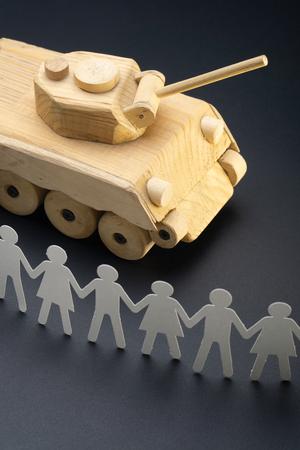 Foto de Raw of paper people rallying in front of a tank. Protest, demonstration toy concept. Activism, social movement. - Imagen libre de derechos