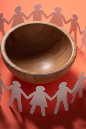 Foto de Circle of paper people holding hands in front of big empty bowl. Overpopulation, famine concept. - Imagen libre de derechos