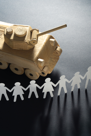 Foto de Raw of paper people rallying in front of a tank. Protest, demonstration toy concept. - Imagen libre de derechos