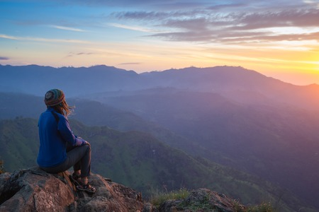 Photo pour Happy celebrating winning success woman at sunset or sunrise standing elated with arms raised up above her head in celebration of having reached mountain top summit goal during hiking travel trek. - image libre de droit