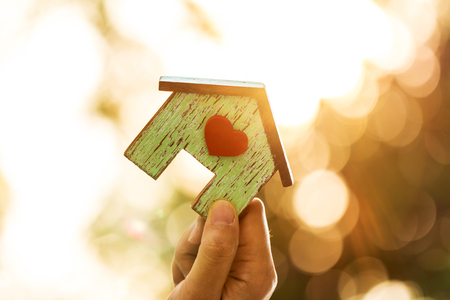 Foto de Women hand holding a home model with red heart in the sunlight in the public park, Loans for real estate or save money for buy a new house to family in the future concept. - Imagen libre de derechos