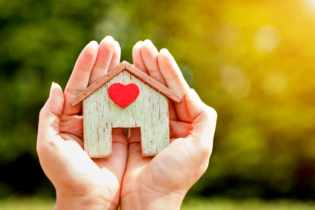 Foto de Woman hand holding a home model stick a red heart in the sunlight in the public park, Loans for real estate or save money to buy a new house for family in the future concept. - Imagen libre de derechos